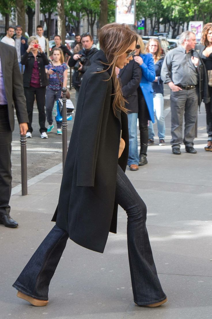 Victoria Beckham in a flared jeans and black jacket thrown over her shoulders