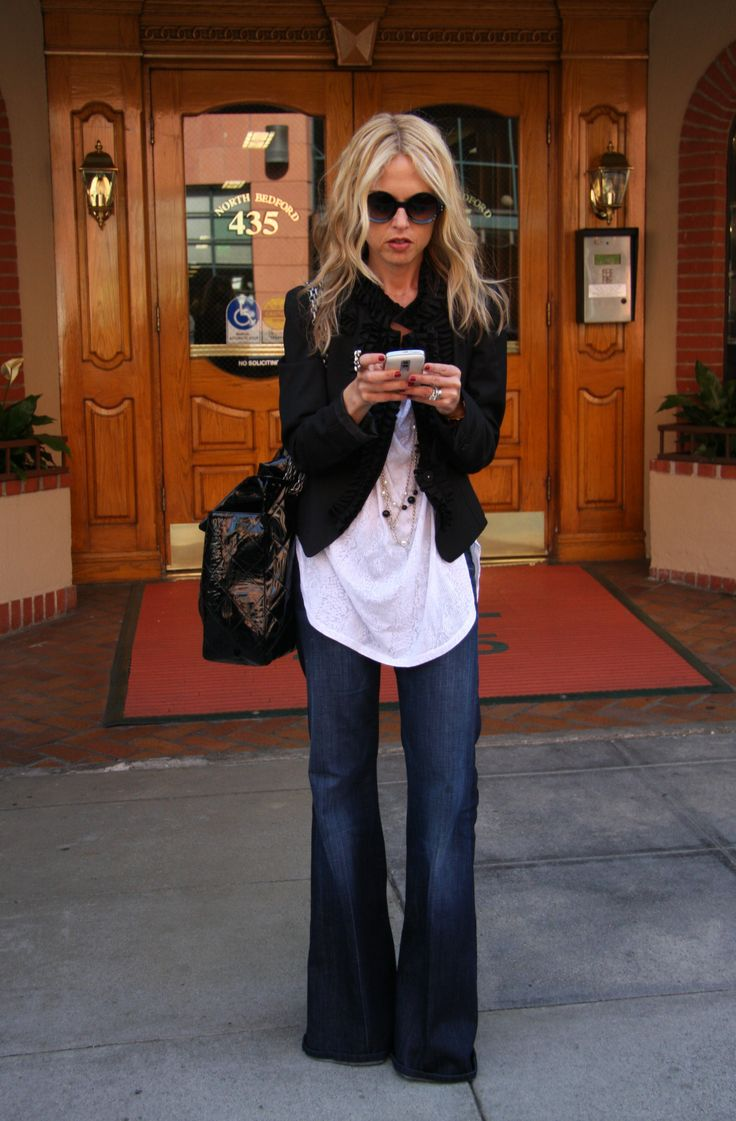Rachel Zoe in a black jacket white shirt and flared jeans